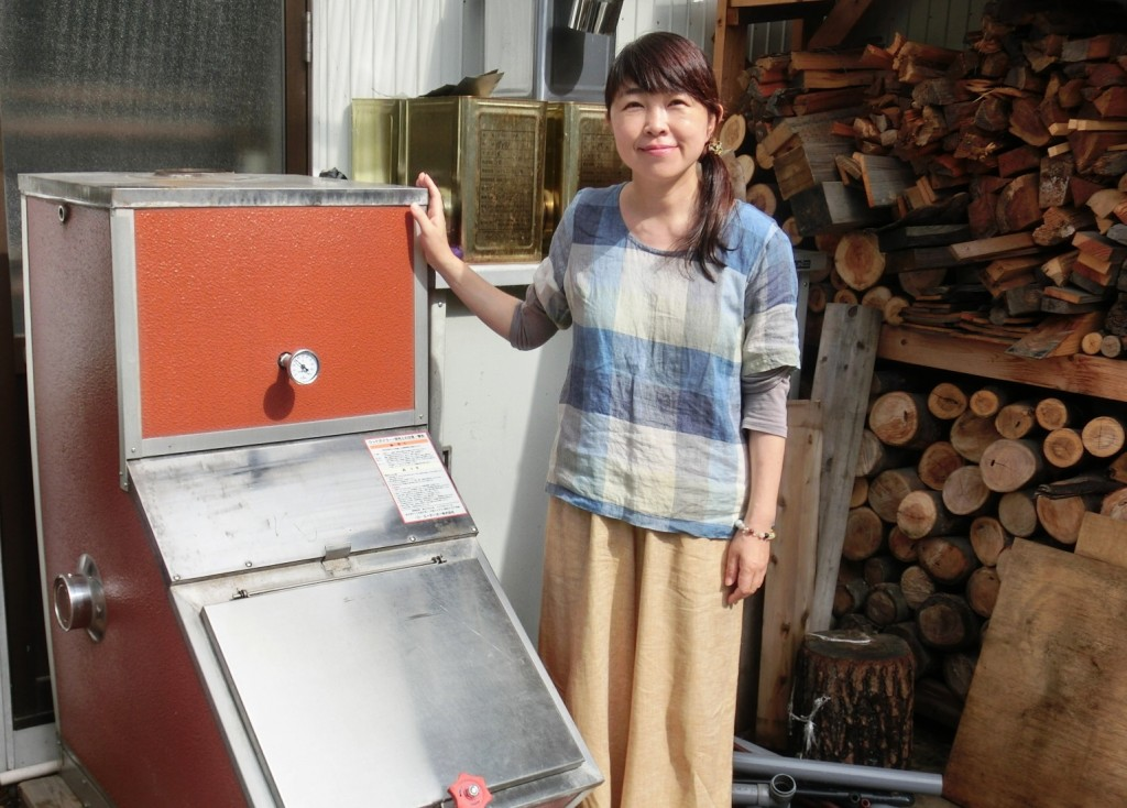 ウッドボイラーデモ機の前で。小田切氏は「全国ご当地エネルギー協会」の北信地区幹事も務める。